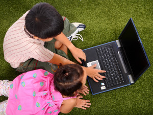 Two Kids Outside On The Grass Browsing The Internet